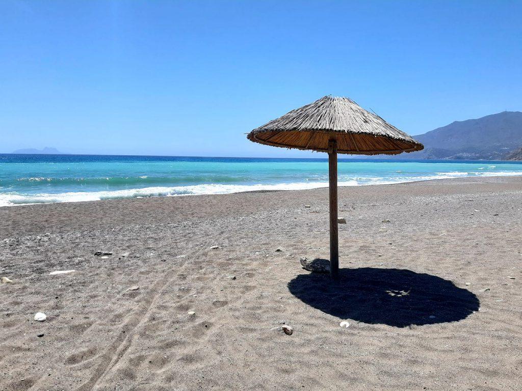 słomiany parasol na pustej plaży